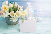 pic of daffodils  - Bright white daffodils and tulips flowers in bucket candles and empty tag in ray of light on turquoise painted wooden planks againsy blue wall - JPG