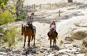 stock photo of cowgirls  - young American Australian man as father or horse instructor of young girl or teen daughter riding little pony wearing cowgirl hat in countryside Summer vacation ride - JPG