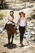 foto of horse-riders  - cute female kid jockey having fun learning riding pony outdoors happy with young Australian American horse instructor woman in cowboy look teaching the little rider in summer nature countryside - JPG