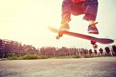 picture of skateboarding  - young skateboarder  legs doing skateboarding trick ollie outdoor - JPG