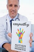 pic of prescription pad  - The word empathy and portrait of a male doctor showing a blank prescription sheet against autism awareness month - JPG