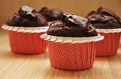 picture of chocolate muffin  - homemade chocolate muffins in red holders on wooden background - JPG
