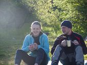 image of mans-best-friend  - A man and a woman drink from mugs on the nature and smile. ** Note: Soft Focus at 100%, best at smaller sizes - JPG