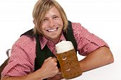 Happy man lying on floor holding oktoberfest beer stein.