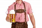 Bavarian man with leather trousers (Lederhose) holds Oktoberfest beer stein.