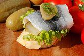 stock photo of baguette  - Baguette slice with sour herring pickled herring garnished with lettuce - JPG