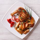 image of thighs  - Grilled chicken thighs and roasted potatoes on a plate - JPG