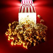 stock photo of popcorn  - Popcorn for a movie in a popcorn holder and spilling out - JPG