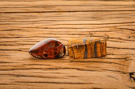 stock photo of tiger eye  - Piece of pietersite and rough tiger eye originating from Namibia Africa on wood - JPG