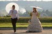 bride and groom walking outside in sun with umbrellas jumping