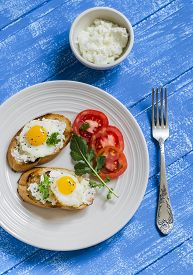 foto of quail egg  - toast with feta cheese and fried quail egg fresh tomatoes on a wooden surface  - JPG