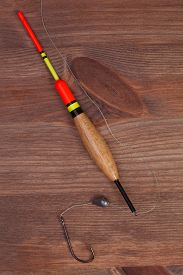 stock photo of fishing bobber  - Fishing tools hook and bobber on a wooden background - JPG
