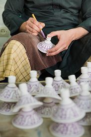 stock photo of pottery  - The artist paint the purple color on the pottery cover in pottery factory name Serghini Maitre Potier et Zellige Fassi in Fes Morocco - JPG