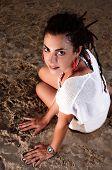 Girl in white dress and dreadlocks on sand
