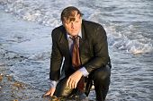 Wet and depressed businessman sitting on the beach