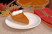 Slice Of Pumpkin Pie With Autumn Leaves Resting In Background