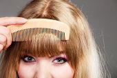 Постер, плакат: Closeup Woman Combing Her Fringe With Comb