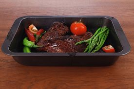 stock photo of peppercorns  - fresh glazed baked big beef meat rib chunk under sweet sauce with tomatoes hot chili pepper asparagus different peppercorn spices in black deep tray on light walnut wooden table - JPG