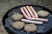 Sausages And Burgers Sizzling On A Barbecue Griddle Plate poster