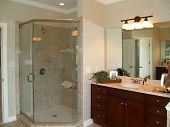 foto of baseboard  - Luxurious marble bathroom with glass enclosed shower and dark wood vanity - JPG