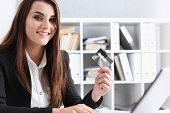 Business Woman In The Office Holds A Plastic Credit Debit Card In Her Hand poster