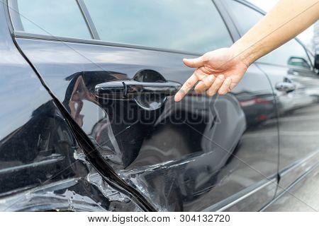 poster of Man Hand Pointing On Car Bumper Dented Broken On Black Car Door. Vehicle Car Crash Damage Accident O