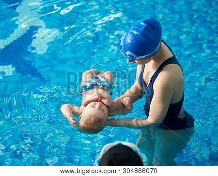 poster of Little Baby Bathing During Health Procedures With Instructor. Trainer In Swimsuit And Swimming Cap H