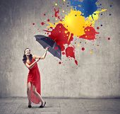 Laughing beautiful woman using an umbrella as a shelter against color drops falling down