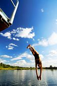 Young man jumping into a lake