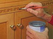 Closeup of painter apply vanish to the inlaid trim of a handcrafted cabinet