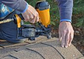 Man using nail gun to attach asphalt shingles to roof