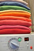 Stack of clothes in colors of the rainbow on top of front-loading washing machine