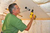 Man using cordless drill to attach drywall panel to ceiling