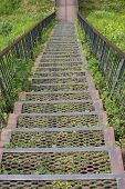 Metal Iron Staircase Leading Down. Metal Steps Iron Railings, Descending From A Green Grassy Hill. O poster