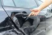 Man Hand Pointing On Car Bumper Dented Broken On Black Car Door. Vehicle Car Crash Damage Accident O poster