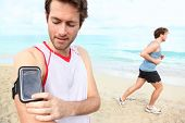 Running workout man with mp3 music player listening to music with mp3 player armband or smart mobile