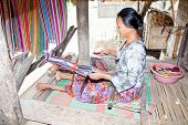 LOMBOK, INDONESIA - FEBRUARY 14 - An elderly weave songket (traditional colorful fabric) using the c
