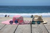 Summer Beach Scene. Sun Hats, Sun Glasses and a BEACH Sign. Beach Board walk with fashion clothes at poster