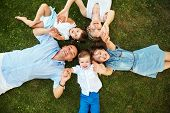 Happy Playful Family Lying On Grass Outdoors. Parents With Children In The Summer. Mom, Dad And Kids poster