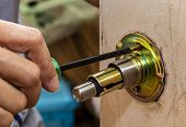 The Locksmith Is Repairing The Wooden Door Knob With Screwdriver. Close Up Of Hand Using Screwdriver poster