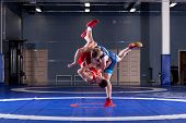 The Concept Of Fair Wrestling. Two Greco-roman  Wrestlers In Red And Blue Uniform Wrestling   On A W poster