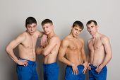 Group of young guys with muscular bodies, naked to the waist.