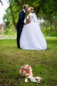 The Groom The Bride On The Background Of The Bouquet. Newlyweds And Wedding Bouquet. Brides Bouquet poster