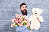Waiting For Darling. Man Well Groomed Wear Tuxedo Bow Tie Hold Flowers Tulips Bouquet And Big Teddy  poster
