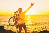Triathlon road bike cyclist carrying bicycle watching sunset after outdoor race training by ocean co poster