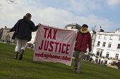 Occupy Exeter activist hold up a Tax Justice banner on Exeter Cathedral green