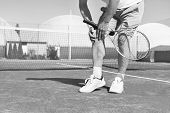 Black and White photo of Low section of mature man holding tennis racket while suffering from knee p poster