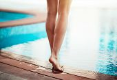 Summer vacation concept, photo of a womens legs, female standing near the pool, barefoot lady with  poster