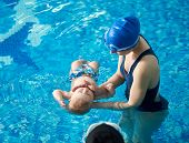 Little Baby Bathing During Health Procedures With Instructor. Trainer In Swimsuit And Swimming Cap H poster