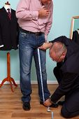 Photo of a man having his inside leg measured by a tailor during a bespoke suit fitting.